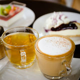 Hot cappuccino and hot tea with cakes. Stock Photos