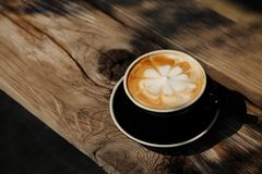 Hot cappuccino latte with flower art pattern in black cup on rustic wooden table with strong morning light royalty free stock image