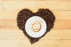 Coffee with love. Hot cappuccino with nice milk pattern in paw and coffee bean heart shape / coffee with love royalty free stock photos