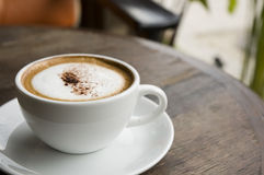 Hot cappuccino at outdoor cafe. A cup of hot cappuccino on table at outdoor cafe Royalty Free Stock Images