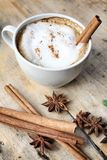 Hot cappuccino with spices cinnamon sticks and star anise. Royalty Free Stock Images
