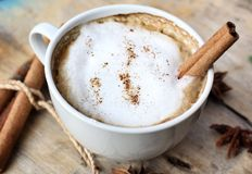 Hot cappuccino with spices cinnamon sticks and star anise. Royalty Free Stock Photo