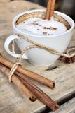 Hot cappuccino with spices cinnamon sticks and star anise. Stock Image