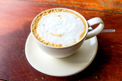 Hot cappuccino in white cup. Hot cappuccino in white cup on wood table Royalty Free Stock Photo