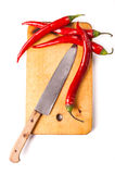 Hot capsicum chili pepper and knife on board Stock Image