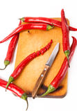 Hot capsicum chili pepper and knife on board Royalty Free Stock Photos
