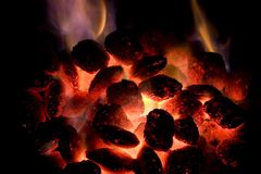 Hot charcoal. Glowing charcoal briquettes with flames stock photography