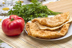 Hot cheburek and tomato with parsley Royalty Free Stock Images
