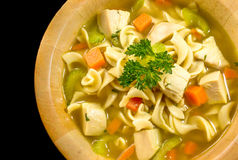 Hot chicken soup. Hot bowl of chicken noodle soup on a dark background royalty free stock photos