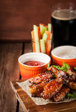 Hot chicken wings cooked with honey and soy, topped with sesame. Spicy hot chicken wings cooked with honey and soy, topped with sesame seeds, served with sauce royalty free stock photo