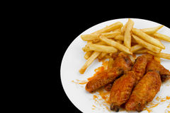 Hot Chicken Wings and French Fries. Isolated on Black Background royalty free stock photos