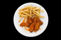 Hot Chicken Wings and French Fries. Isolated on Black Background royalty free stock photography