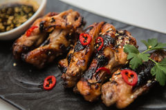 Hot chicken wings. Hot organic chicken wings with red pepper on black dish Stock Photography