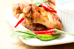 Hot chicken wings on plate on wooden table. Hot chicken wings on plate with chilli peppers stock photo