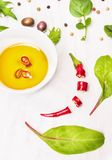 Hot chili oil, olives and salad leaves Stock Photos