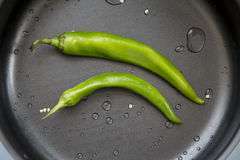Hot chili pepper. And green in the pan Stock Image