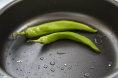 Hot chili pepper. And green in the pan Royalty Free Stock Photo