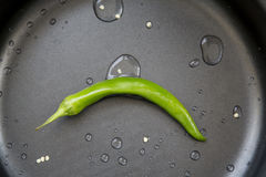 Hot chili pepper. And green in the pan Stock Photo