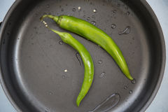 Hot chili pepper. And green in the pan Royalty Free Stock Images