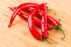 Hot chili pepper on wooden texture. Royalty Free Stock Photo