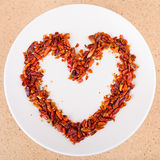 Hot chili peppers arranged in heart shape Stock Photos