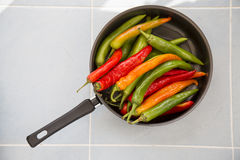 Hot chili peppers of different colors. A lot of hot chili peppers of different colors in the pan Stock Photo