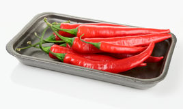 Hot chili peppers in retail pack. Isolated with shadow and reflection stock photos
