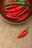 Hot chili peppers in wooden bowl over canvas stock image