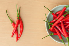 Hot chili peppers on the wooden desk. Red hot chili peppers on the wooden desk Stock Photography