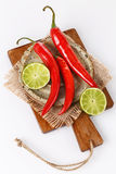 Hot chilli and lime over white background Stock Photos