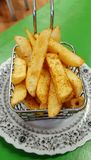 Hot chips. Hot chips in metal basket on vintage plate. Sitting on green coloured table Royalty Free Stock Images