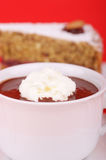 Hot chocolate. A cup of hot chocolate with whipped cream and a piece of buckwheat cake in the background. Selective focus. Extremely shallow DOF Royalty Free Stock Photography