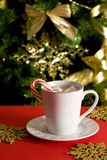 Hot Chocolate. A cup of a hot chocolate with marshmallow and candy cane against a Christmas tree Royalty Free Stock Images