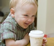 Hot chocolate. Young boy smiles while drinking hot chocolate stock images