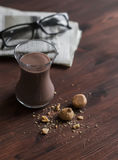 Hot chocolate, almond cookies and newspapers on dark brown wooden surface. Royalty Free Stock Photo