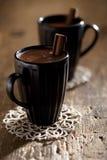 Hot chocolate in black mugs with cinnamon Stock Photo