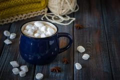 Hot chocolate or cacao in a blue mug with marshmallows on the ta. Ble with wool Stock Photos