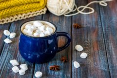 Hot chocolate or cacao in a blue mug with marshmallows on the ta. Ble with wool Royalty Free Stock Photo