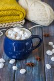 Hot chocolate or cacao in a blue mug with marshmallows on the ta. Ble with wool Royalty Free Stock Images