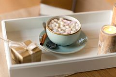 Hot chocolate, christmas gift and candles on table. Holidays and still life concept - hot chocolate with marshmallow, christmas gift and candles on table stock photos