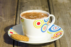 Hot chocolate with cinnamon and biscuit on wood Royalty Free Stock Images