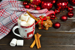 Hot chocolate or cocoa beverage with cinnamon and gingerbread cookies in snow vintage wooden table background. Royalty Free Stock Image
