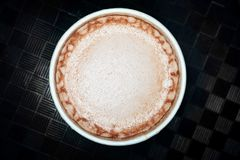 Hot chocolate cocoa drink close up macro foam texture on dark background royalty free stock photography