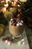 Hot chocolate or cocoa drink, with marshmallows on Christmas background. With lights stock photography