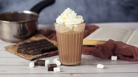 Hot chocolate or cocoa in glass with whipped cream, marshmallow and pieces chocolate Royalty Free Stock Images