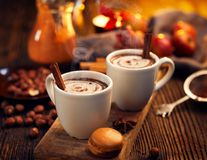 Hot chocolate with cream, sprinkled with aromatic cinnamon in white cups. On a rustic wooden table royalty free stock photography