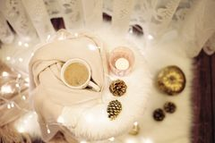 Hot chocolate, a cup of cappuccino on a fur chair. Warm scarf, cones, lights around. Cozy winter evenings. Hot chocolate, a cup of cappuccino on a fur chair stock photography