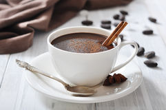 Hot Chocolate in cup. With cocoa powder and cinnamon stick on wooden background Royalty Free Stock Photos