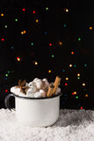 Hot chocolate in cup with marshmallow and spices on the snow with christmas lights background. Copy space royalty free stock image