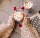 Hot chocolate cup with marshmallow in a woman hand. With Laptop and  tiny Santana Claus hats in the background Stock Photo